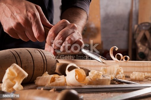 istock Hands of craftsman carve  with a gouge 586934716