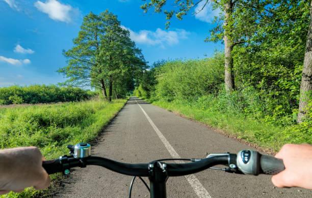 hände des fahrers am lenker radfahren auf spur durch sommerlandschaft mit bäumen und weide - radwege deutschland stock-fotos und bilder