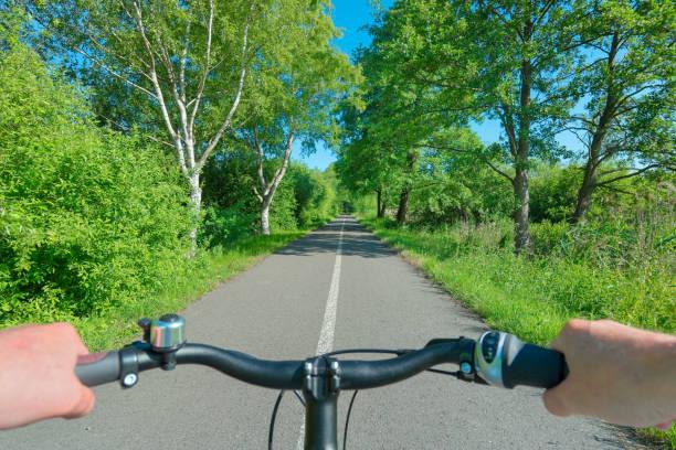hände des fahrers am lenker radfahren auf bäumen gesäumt lane durch sommerlandschaft - radwege deutschland stock-fotos und bilder