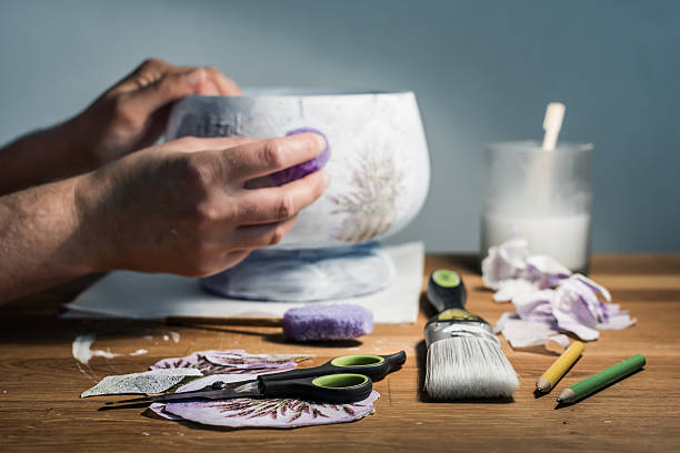 hands of decoupage artist and artistic supplies on the table. - decoupage kunst stock-fotos und bilder