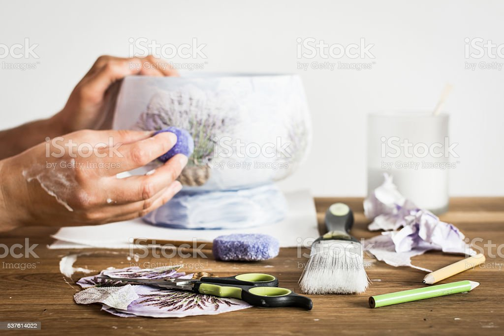 Hands of decoupage artist and craft supplies on the table. stock photo