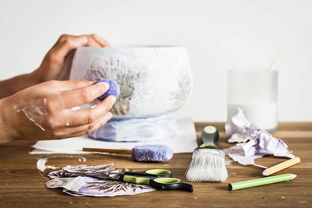 hands of decoupage artist and craft supplies on the table. - decoupage kunst stock-fotos und bilder