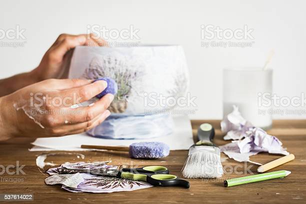 Decoupage artist workshop: scissors, sponge, paintbrush, pencils and paint. Hands of a hobbyist decorating a vase with lavender pattern.