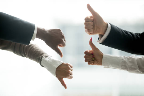 Hands of diverse business people showing thumbs up and down Hands of diverse business people showing thumbs up and down, like versus dislike gesture, positive negative feedback, yes and no opposition voting, confrontation disagreement at negotiations concept debate stock pictures, royalty-free photos & images