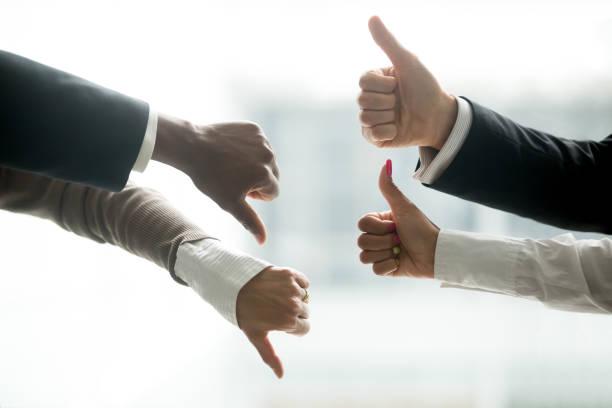 hands of diverse business people showing thumbs up and down - debate стоковые фото и изображения