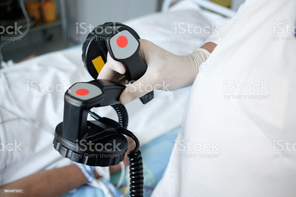 hands of doctor holding defibrillator electrods, ready for defibrillation or electropulse therapy stock photo