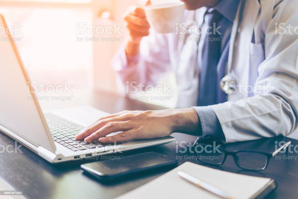 Hände des Arztes mit seinem Laptop mit Kaffeetrinken – Foto
