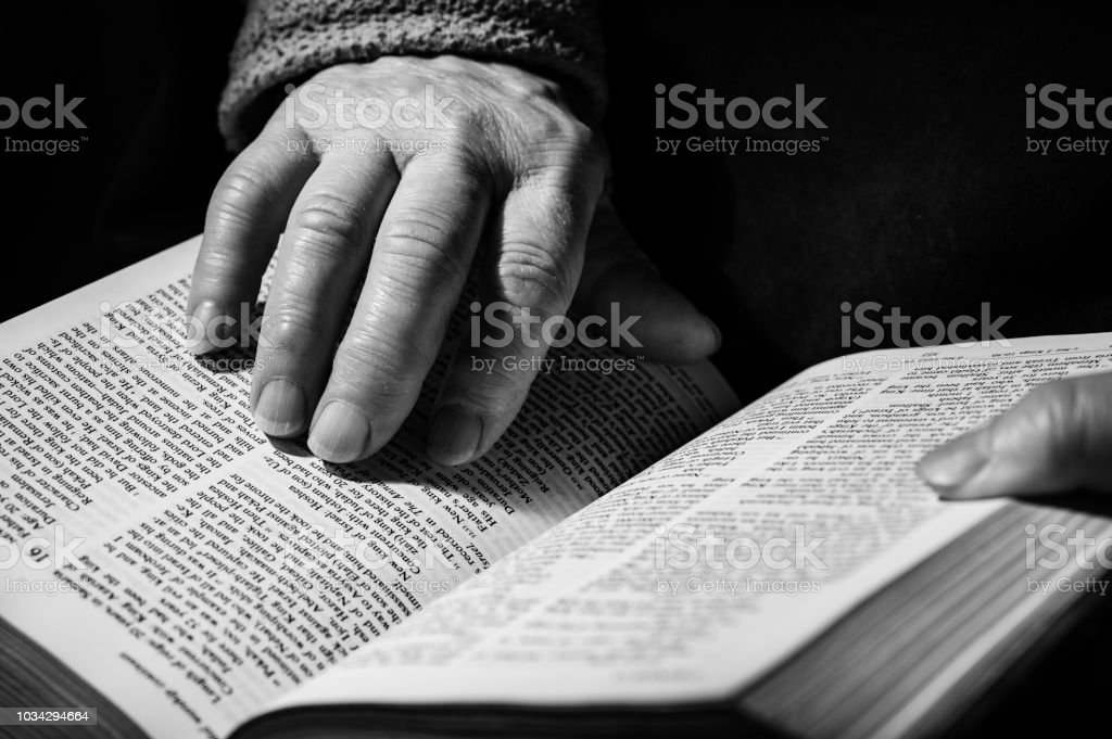 Hands Of Elderly Woman While Read Bible And Pray Stock Photo