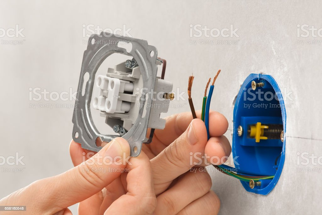 Hands Of Electrician Installing Light Switch In Plasterboard ... on