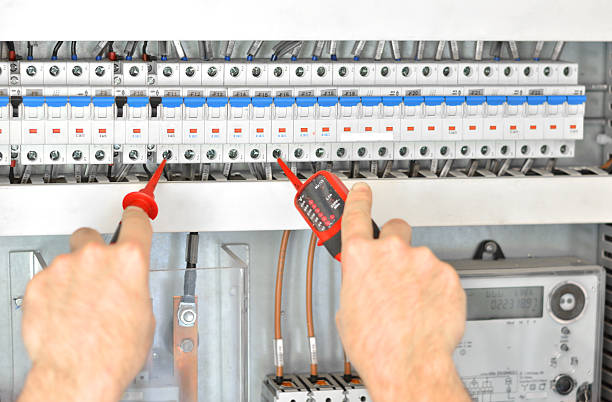 Hands of Electrician Testing for Voltage in a Fuse Box stock photo