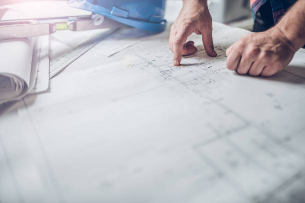 Hands of Engineer working on blueprint stock photo