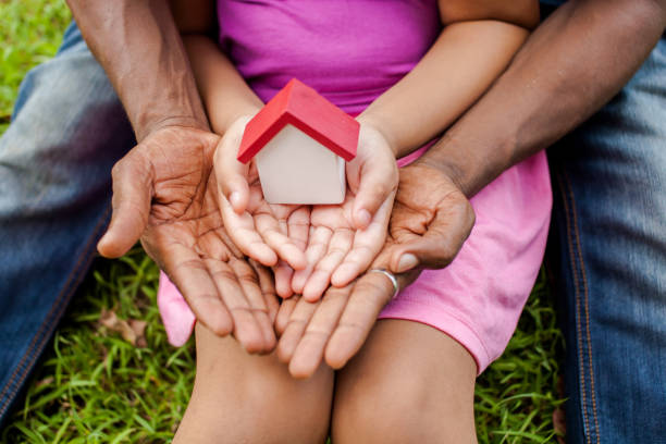 hands of family together holding house in green park - wohnungsprobleme stock-fotos und bilder