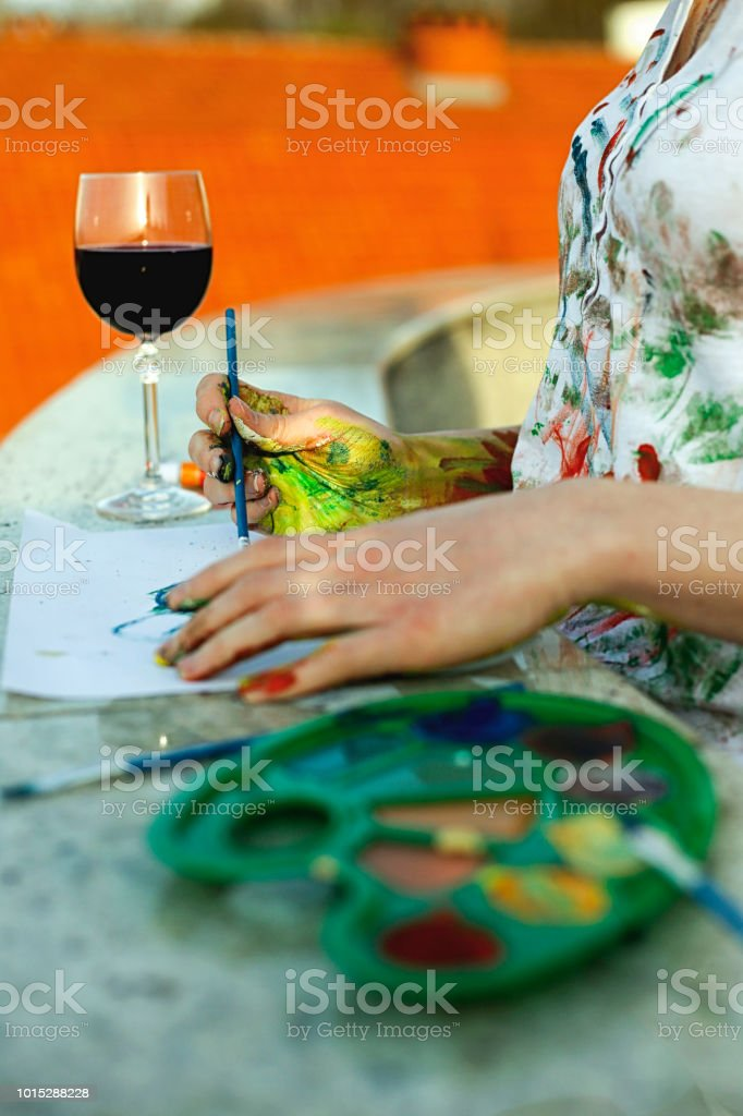Hands of female artist holding messy dirty palette with different paints and paintbrush in art studio. Lifestyle and hobby concept stock photo