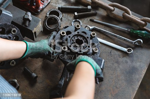 Industrial plant worker repairing car parts in auto repair workshop - Mechanical engineer inspecting and adjusting vehicle part - Manufacturing factory, student apprentice and skilled work concept