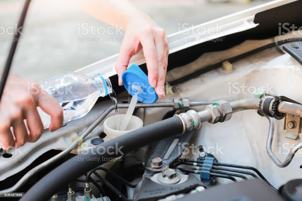 Hands of filling fresh water into the canister of the car windscreen wiper system. stock photo