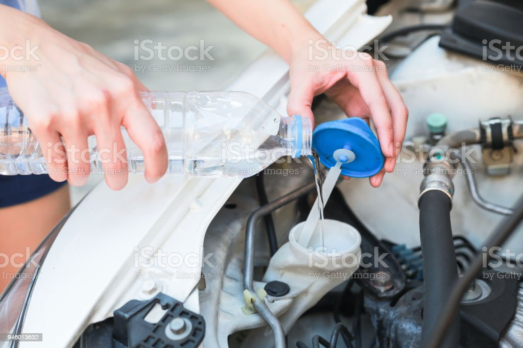 Hands of filling water into the canister of the car windscreen wiper system. stock photo