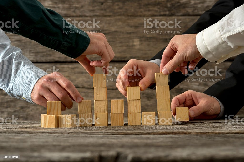 Hands of five businessman holding wooden blocks placing them int Hands of five businessman holding wooden blocks placing them into a structure. Conceptual of teamwork, strategy and business start up. 2015 Stock Photo