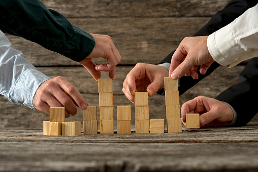 Hands Of Five Businessman Holding Wooden Blocks Placing Them Int Stock Photo - Download Image Now