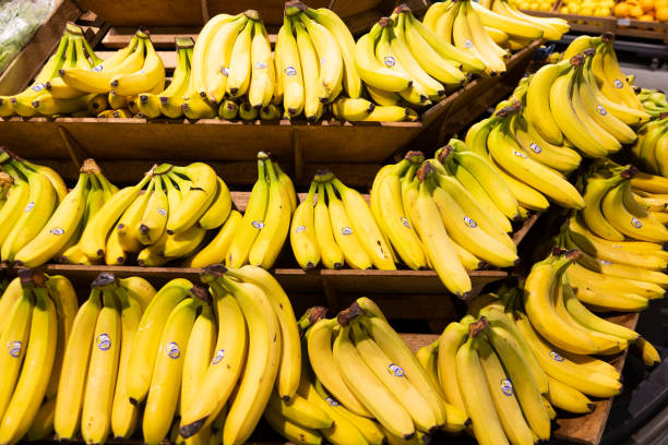 Hands of fresh yellow bananas on wooden shelves in groceries stock photo