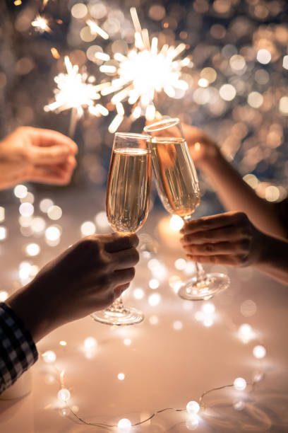 hands of friends holding flutes of champagne and sparkling bengal lights - shironosov stock pictures, royalty-free photos & images