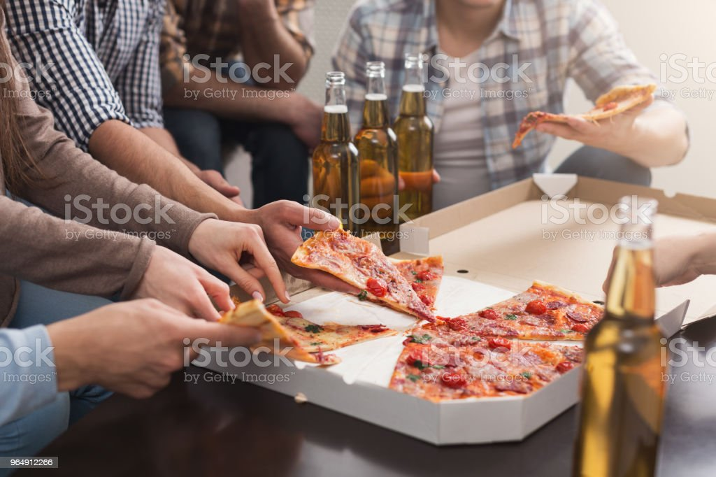 Hands of friends taking slices of tasty pizza at home royalty-free stock photo
