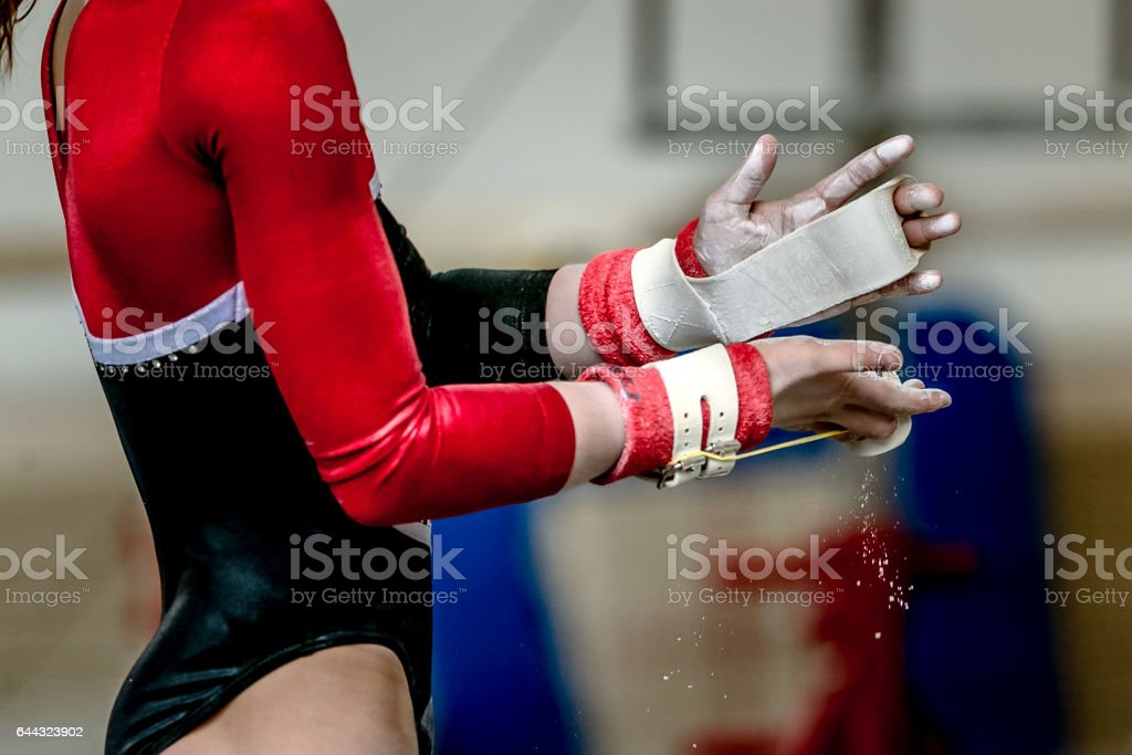 hands of girl in gymnast grips before performing on horizontal bar stock photo