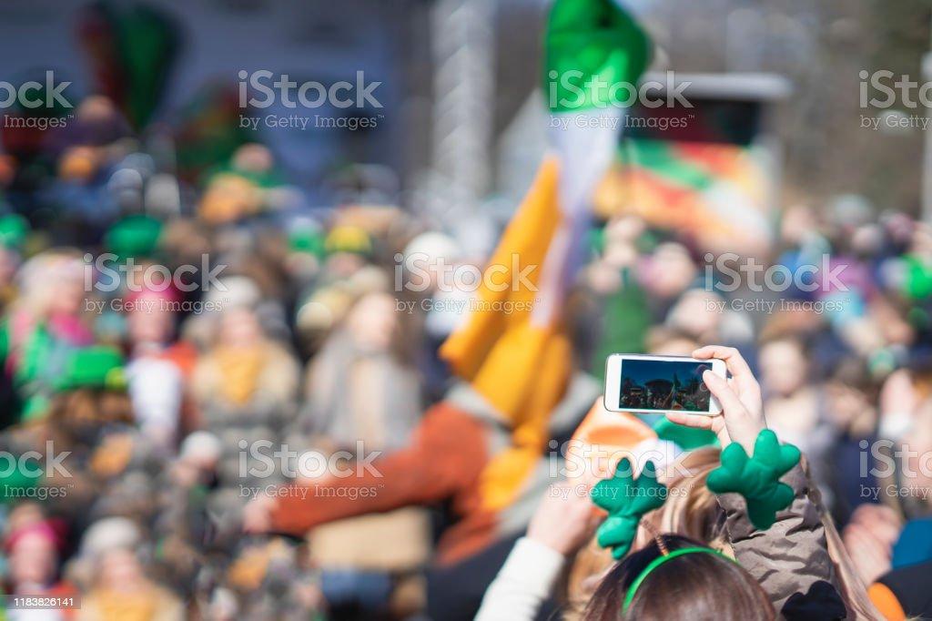 Cep telefonu ile kız Eller, St Patrick Günü karnaval fotoğraf yapma, bir akıllı telefon geleneksel karnaval partisi - Royalty-free Adamlar Stok görsel