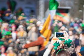 Hands of girl with mobile phone, making photo, video of carnival of St. Patrick's Day, traditional carnival party on a smartphone