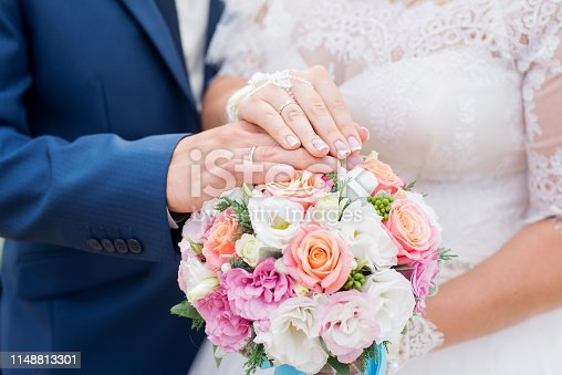 istock Hands of groom and bride with wedding rings and flowers bouquet. concept of love and marriage 1148813301