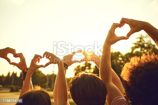 Hands of group friends in the shape of a heart against the sunset. Love and relationship friendship concept