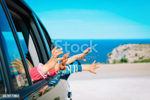 915609494istockphoto hands of happy kids travel by car on beach 947811364