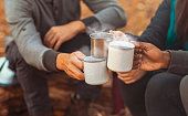 Hands of international hikers cheering up with camping cups, camping in forest, close up