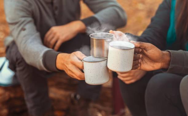 manos de excursionistas animando con tazas de camping - café bebida fotografías e imágenes de stock