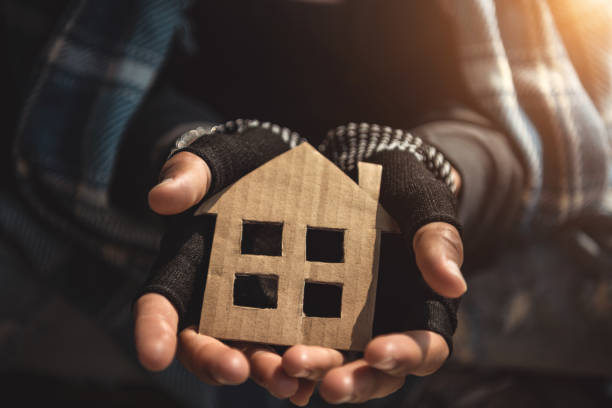 Hands of Homelessness Poor man holding the paper house hope to have family home and warm home Hands of Homelessness Poor man holding the paper house hope to have family home and warm home homelessness stock pictures, royalty-free photos & images