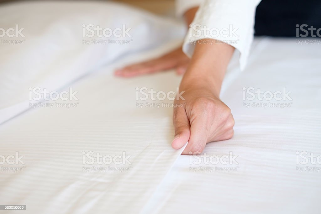 Hands of hotel maid making a room bed stock photo