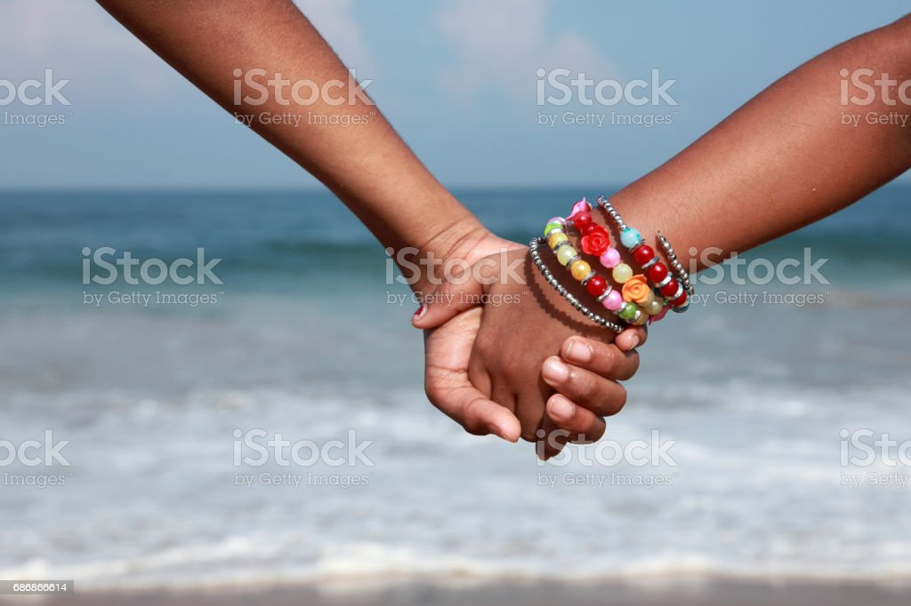 Hands of kids hold together in a beach stock photo