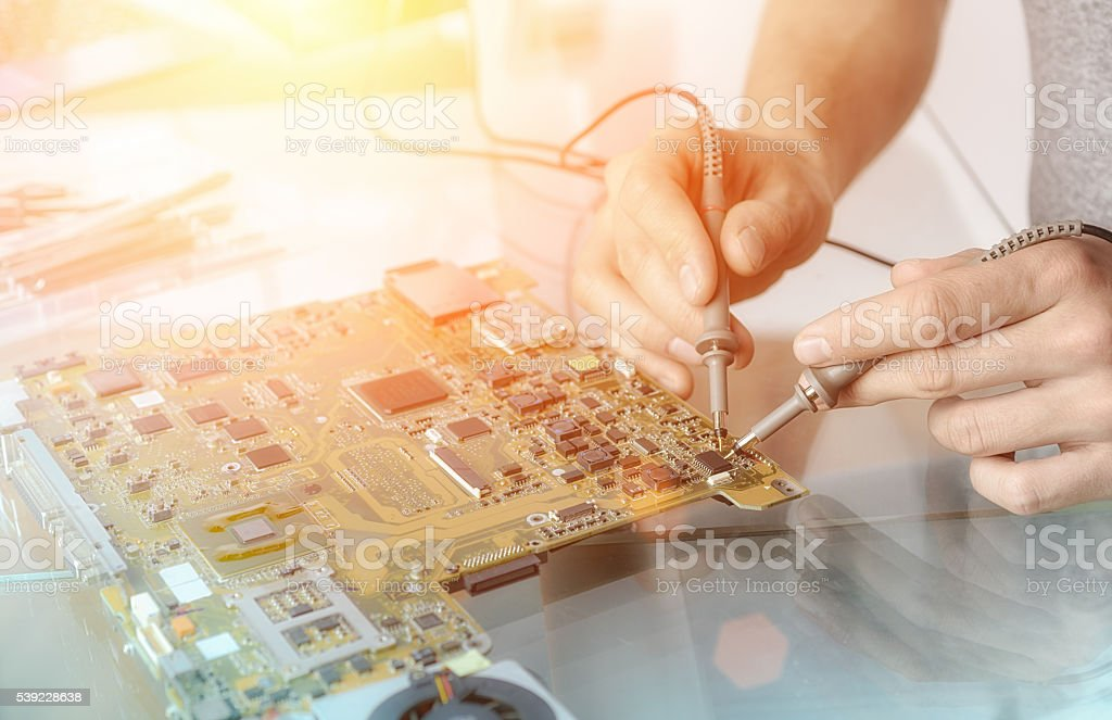 Hands of male tech testing motherboard stock photo
