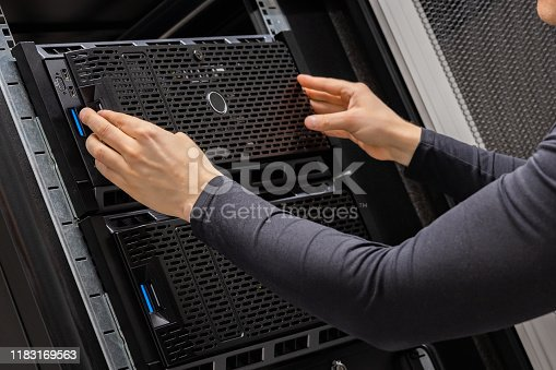 istock Hands Of Male Technician Installing Servers In Datacenter 1183169563