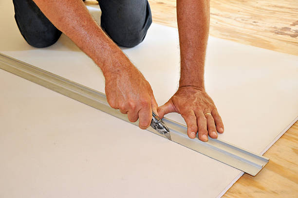 Hands of man cutting drywall with utility knife stock photo