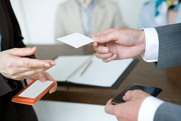 Hands of man handing business card stock photo