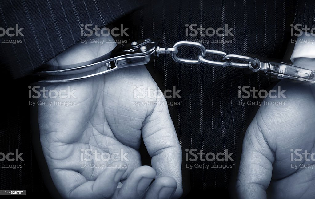 Hands of man in suit in handcuffs stock photo