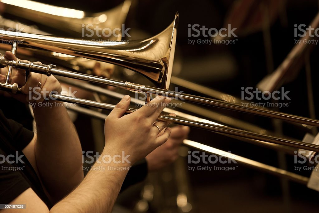 Hands of man playing the trombone stock photo
