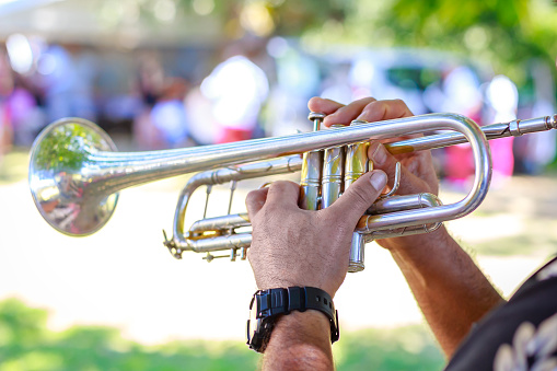 istock Hands of man playing the trumpet at outdoor 615738932