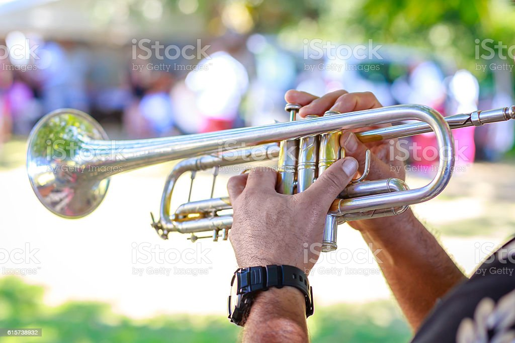 Hands of man playing the trumpet at outdoor stock photo