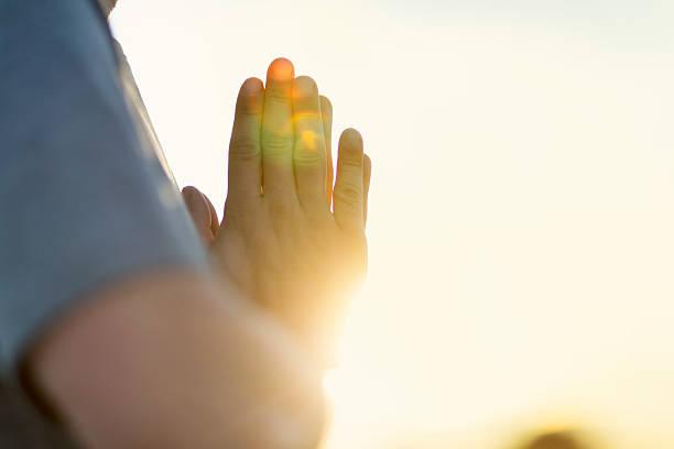 Hands of man praying at sunset – Foto