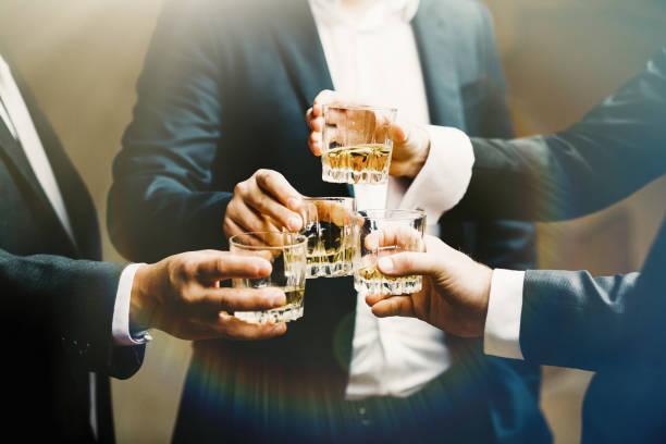 mains du mans avec verres de whisky, célébrer et faire griller - spiritueux photos et images de collection