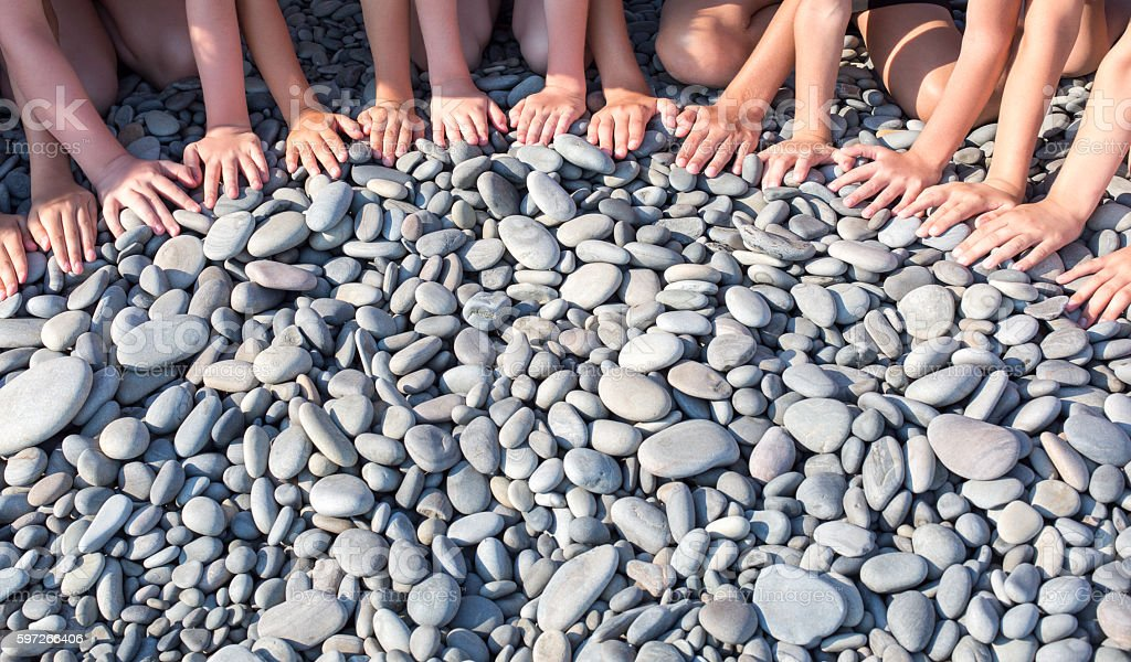 Hands of many children form a semicircle on the beach Lizenzfreies stock-foto