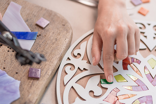 istock Hands of master working on new modern colorful mosaic. Close-up 1002148622