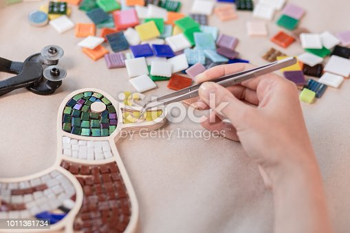 istock Hands of master working on new modern colorful mosaic. Close-up 1011361734