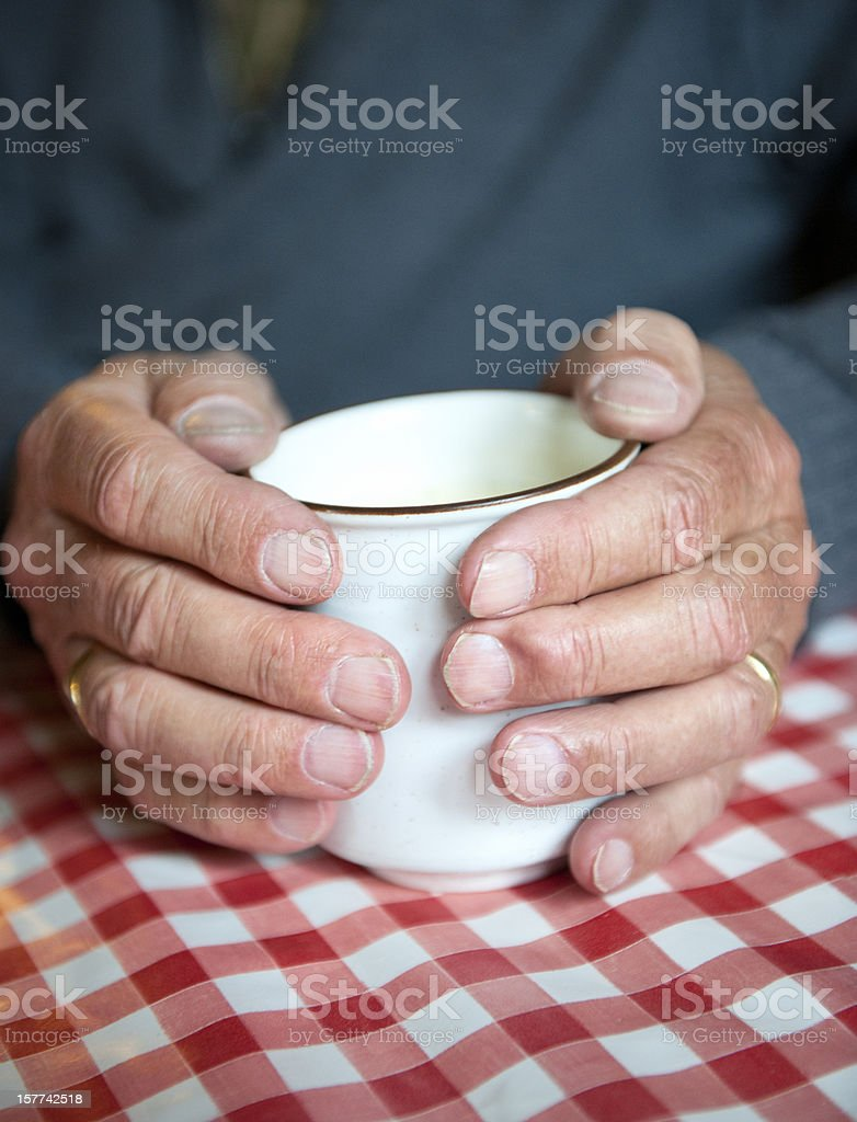 hands of mature man holding a cup royalty-free stock photo
